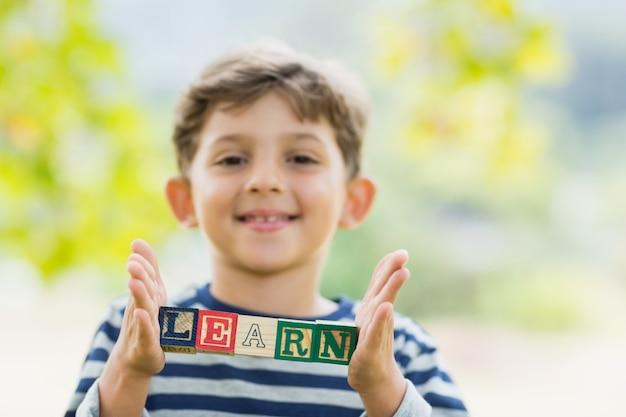 学ぶ公園でブロックを保持している少年を学ぶ