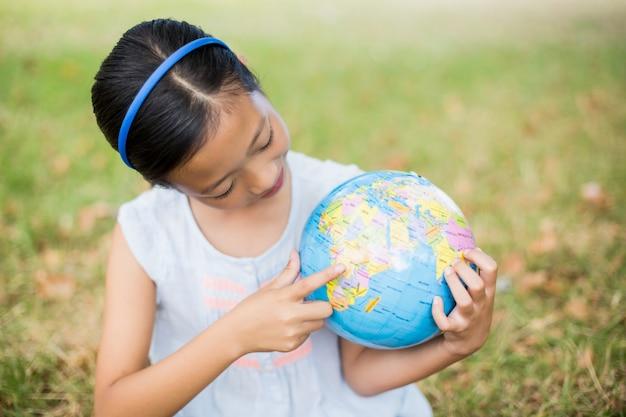Улыбающаяся девушка, глядя на глобус