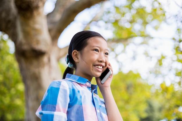 Улыбающаяся девушка разговаривает по мобильному телефону