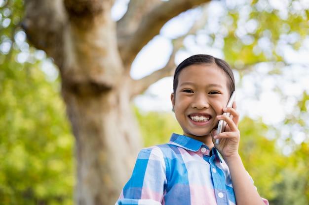 Портрет улыбающейся девушки разговаривает по мобильному телефону