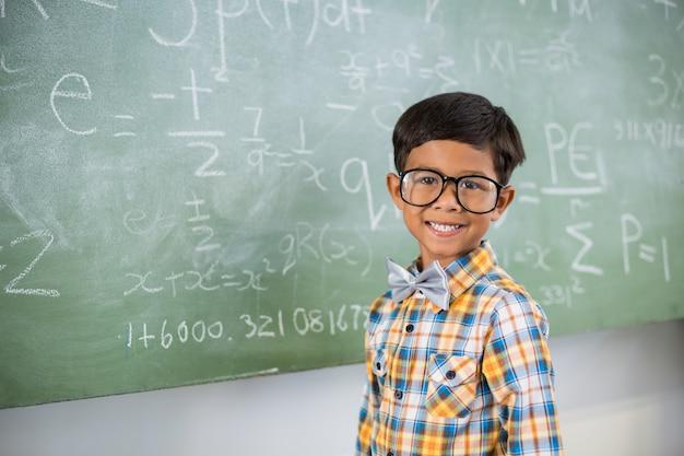 教室で黒板に対して笑みを浮かべて少年の肖像画