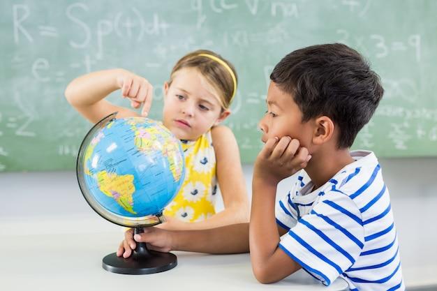 Школьники, глядя на глобус в классе