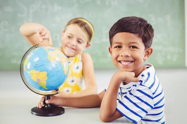 Счастливые школьники с глобусом в классе