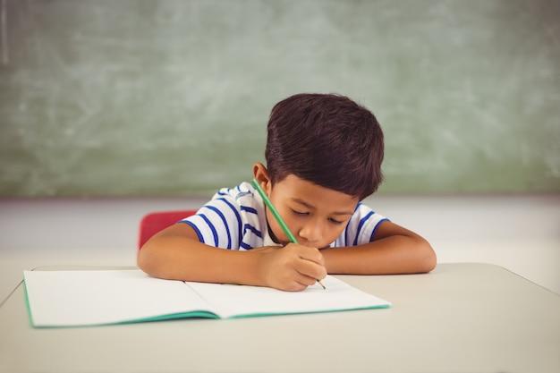 教室で宿題をしている少年