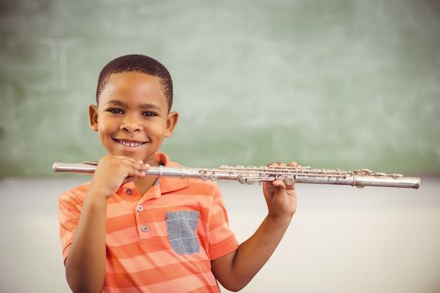 教室でフルートを演奏する少年の笑顔の肖像画