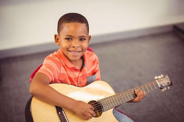 教室でギターを弾く少年の笑顔
