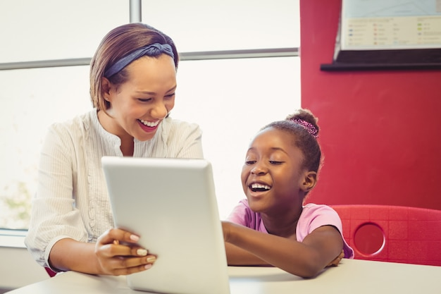教室で教師と学校の女の子がデジタルタブレットを使用して
