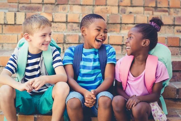 階段に一緒に座って幸せな学校の子供たち