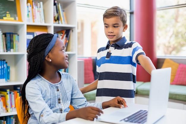 図書館でラップトップを使用して学校の子供たち