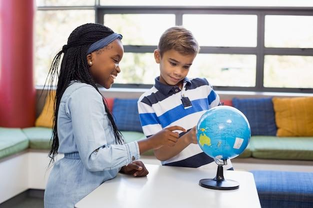 Школьники, глядя на глобус в библиотеке