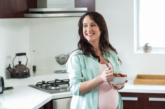 Беременная женщина ест кашу на кухне