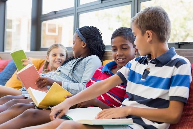 学校の子供たちはソファに座って、図書館で本を読んで