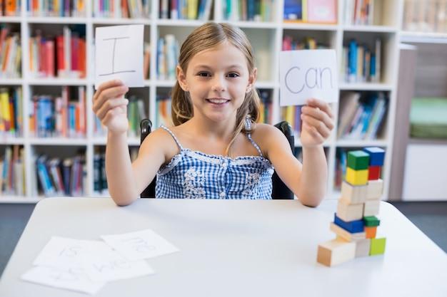 私は図書館で読むことができるプラカードを保持している障害者の少女