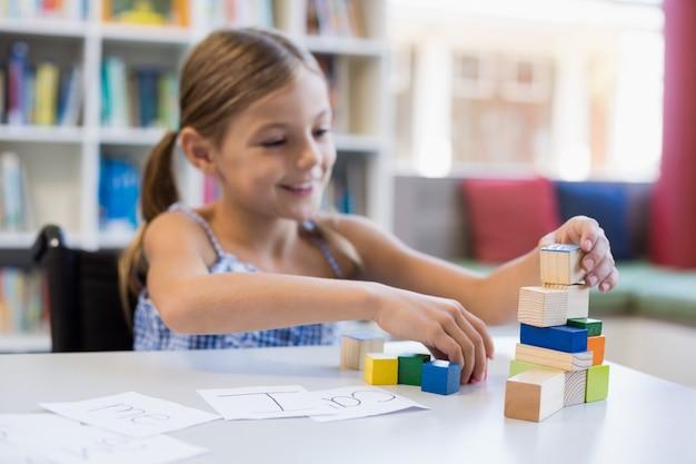 図書館のビルディングブロックで遊んで笑顔の学校の女の子