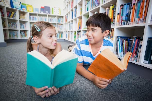 学校の子供たちは床に横たわって、図書館で本を読んで