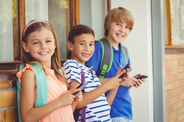 廊下で携帯電話を使用して学校の子供たちの肖像画