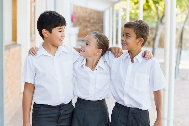 廊下で腕を組んで立っている笑顔の学校の子供たち