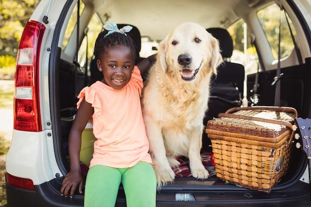 彼女の犬とポーズをとって幸せな女の子