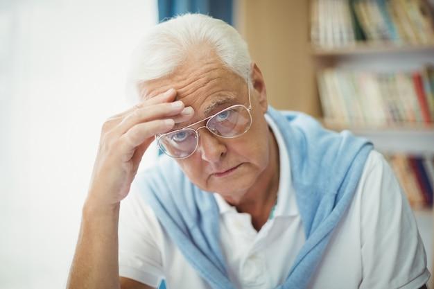 Грустный старший мужчина сидит за столом