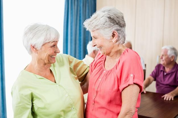 Улыбающиеся старшие женщины, глядя друг на друга