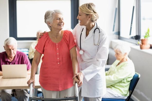 Медсестра помогает старшему с ходьбой