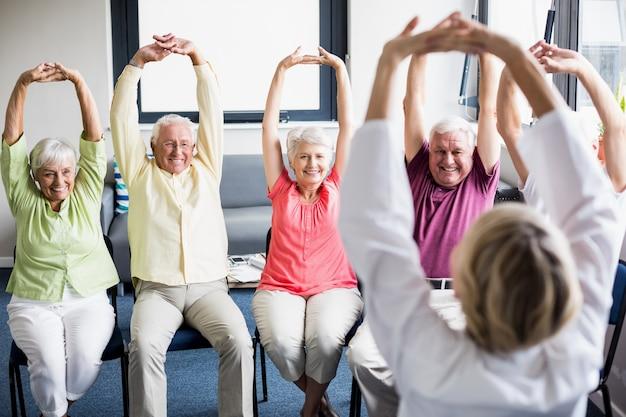 Пожилые люди делают упражнения