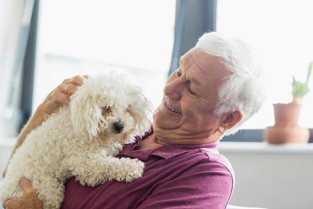 犬を保持している年配の男性