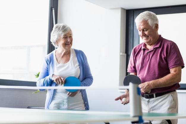 Пожилые люди играют в пинг-понг