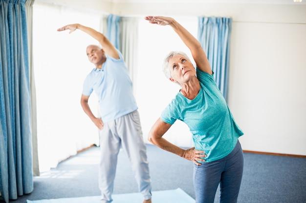 Пожилые люди делают растяжку