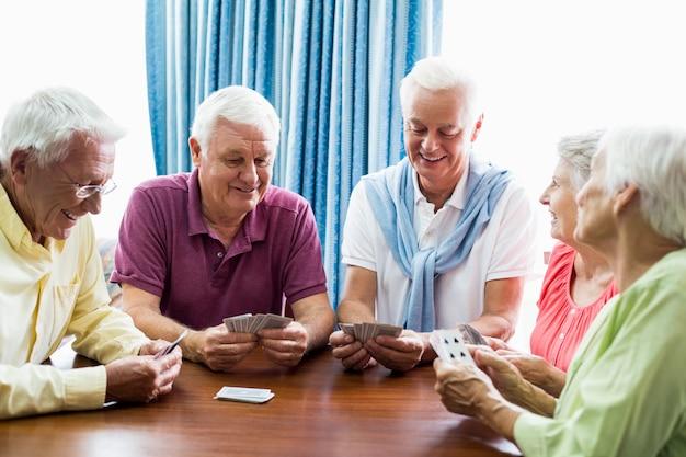 Пожилые люди играют в карты вместе