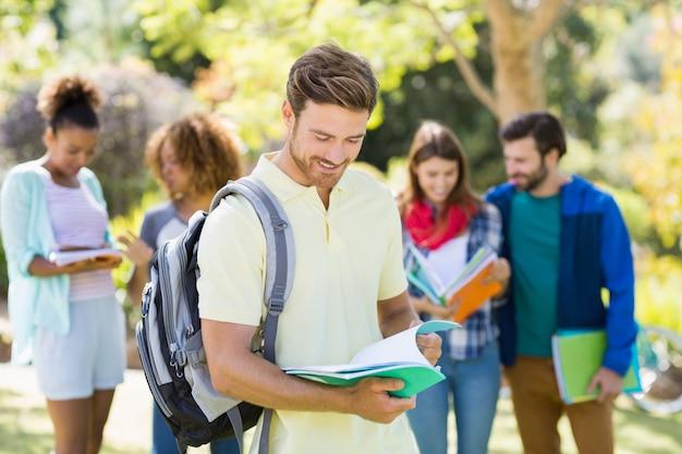 Студент колледжа читает заметки с друзьями