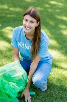 Портрет женщины-добровольца, собирающей мусор