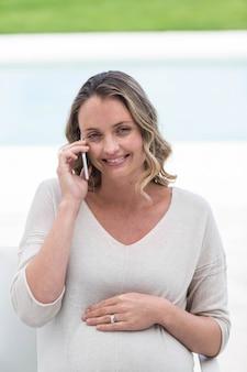 妊娠中の女性がプールサイドで電話をかける
