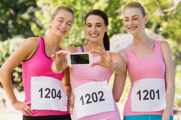 Молодые женщины спортсмена принимая фото с мобильного телефона