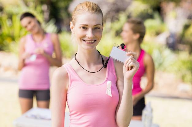Женский волонтер, показывающий ее удостоверение личности