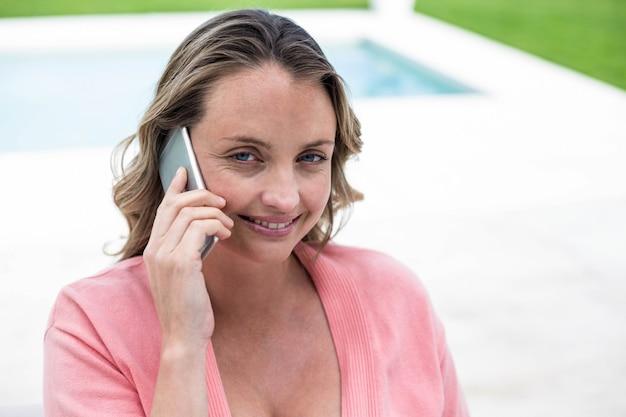 Беременная женщина звонит по телефону у бассейна