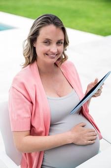 Беременная женщина с помощью планшета у бассейна