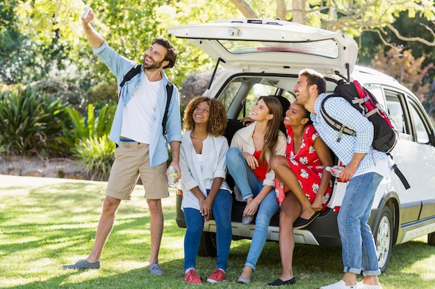 Группа друзей, принимая селфи из багажника автомобиля