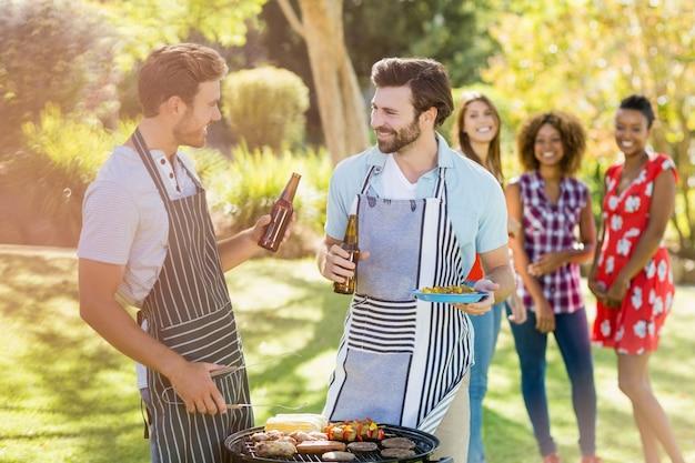 Мужчины держат бутылку пива во время приготовления барбекю