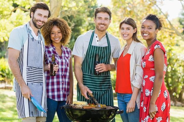 Портрет счастливых друзей готовит барбекю в парке