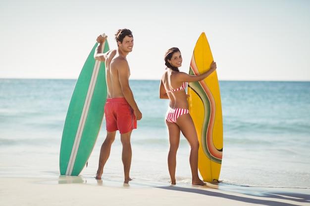 カップルはビーチでサーフボードに立っています。
