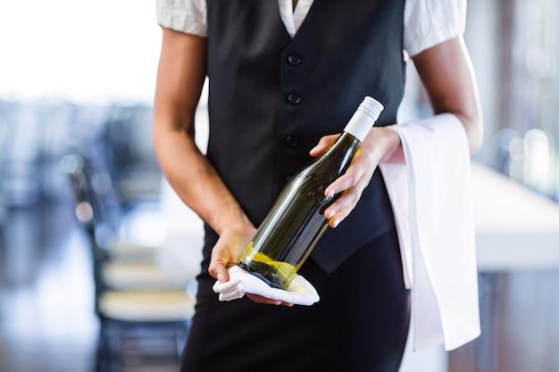 白ワインのボトルとタオルを保持しているウェイトレスの中央部