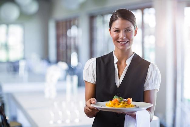 レストランでの食事のプレートを保持しているウェイトレス