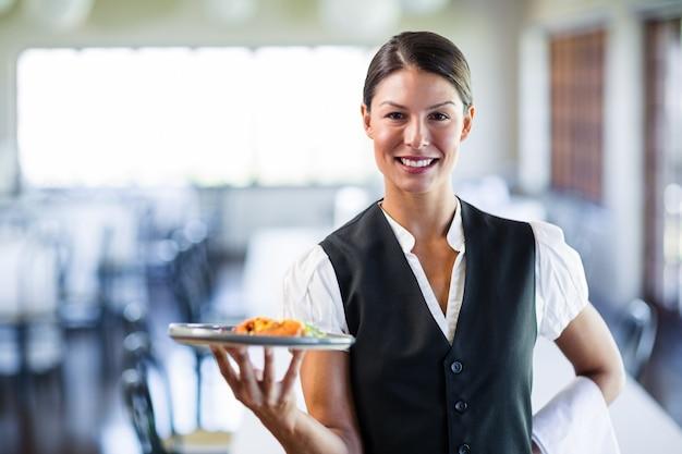 レストランで食事のプレートを保持しているウェイトレス
