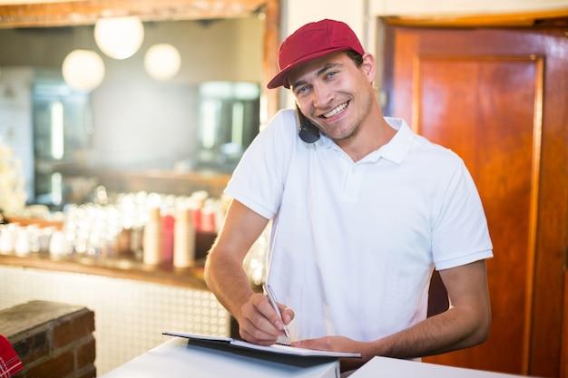 Доставщик пиццы принимает заказ по телефону