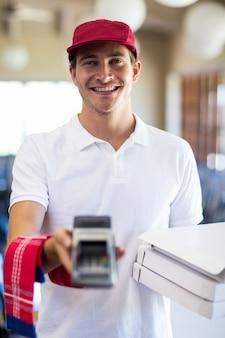 クレジットカードマシンを示す幸せなピザ配達人