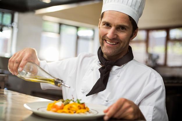 Портрет счастливого шеф-повара наливая оливковое масло на еду