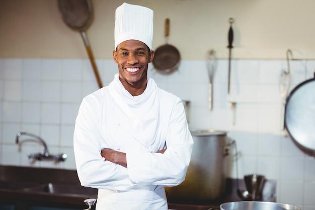 Портрет счастливого шеф-повара, стоя со скрещенными руками