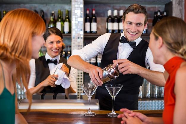 バーテンダーが飲み物を準備しながらカウンターに立っている友人