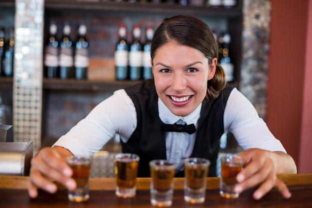 バーカウンターにショットグラスを配置するバーテンダーの肖像画